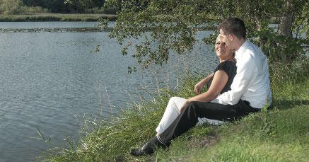 Paar auf einer grünen Wiese am See