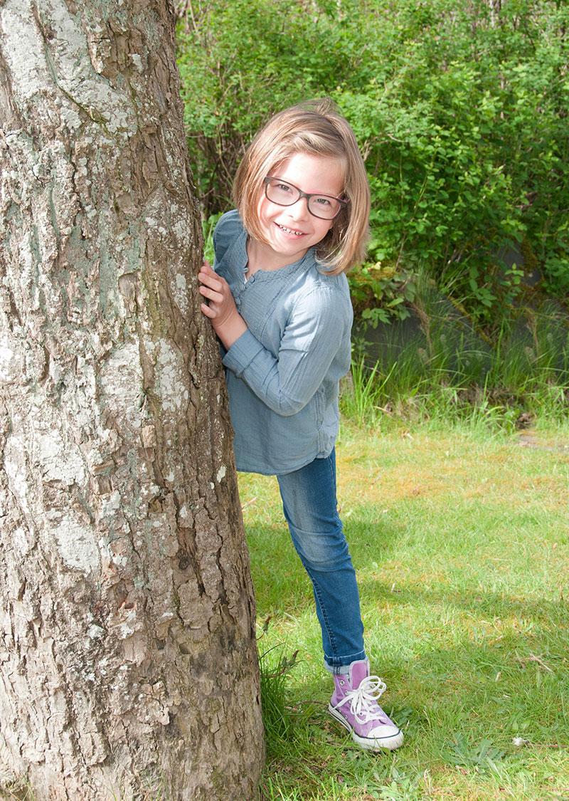Mädchen hinter einem Baum